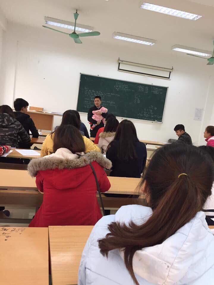 Thầy giáo bế con cho sinh viên làm bài thi