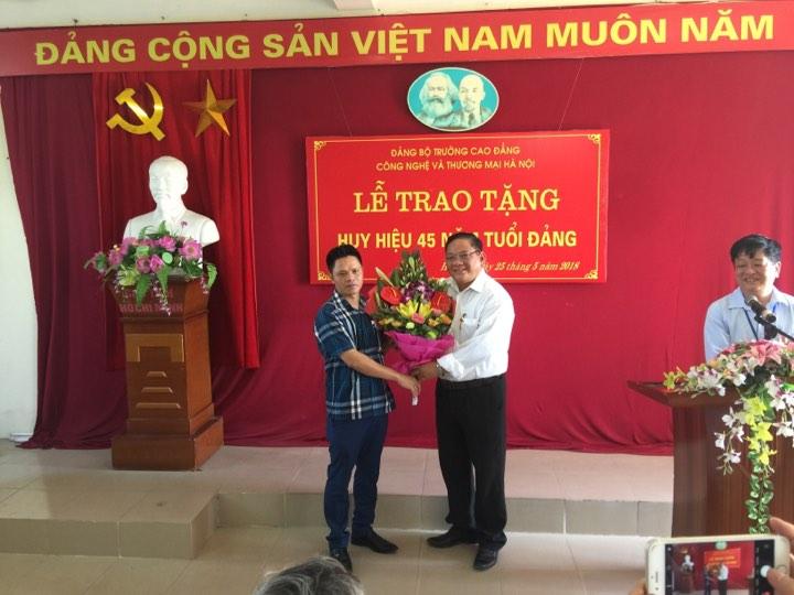 Đại diện Ban Giám hiệu, TS. Nguyễn Xuân Sang - Hiệu trưởng Nhà trường tặng hoa chúc mừng đ/c Nguyễn Văn Phong